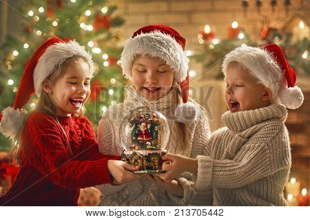 Merry Christmas and Happy Holiday! Cute little children with snow globe near tree at home.