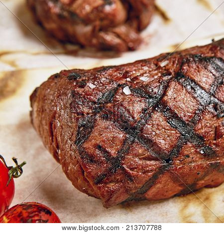 Gourmet Grill Restaurant Steak Menu - Chateaubriand Beef Steak on Parchment. Black Angus Prime Beef Steak. Beef Steak Dinner