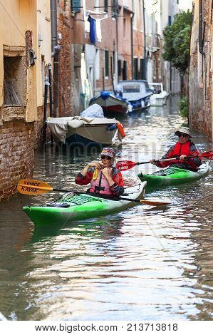 VENICE ITALY - SEPTEMBER 22 2017: City tour by tourists with kayak narrow channel. Communication in the city is done by water which creates a network of 150 channels interconnected.