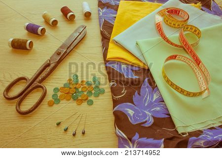 Furniture and equipment for sewing in designer sewing workshop. tools for sewing for hobby. instruments sewing craft on wooden background close up - Retro color