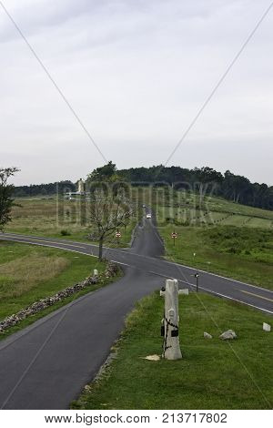 Gettysburg, Pennsylvania - September 9, 2009 - Vertical of a cross roads with memorials to the fallen Civil War Soldiers in a battlefield in Gettysburg Military Park, Pennsylvania late afternoon on a cloudy day in September.