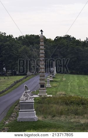 Gettysburg, Pennsylvania - September 9, 2009 - Vertical of a road lined with memorials to the fallen Civil War Soldiers in Gettysburg Military Park, Pennsylvania at sunset on a cloudy day in September.