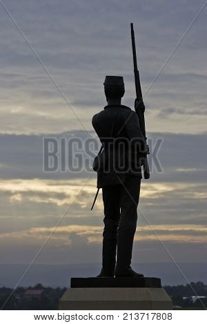 Gettysburg, Pennsylvania - September 9, 2009 - Vertical close up of a statue in silhouetted of a Civil War Soldier with long rifle in hand overlooking the battlefields of Gettysburg Military Park, Pennsylvania at sunset on a cloudy day in September.
