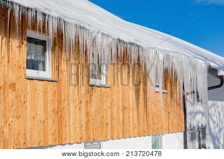 Big icicles on the roof of the cottage in winter. Daylight fades over a snow-covered suburban home. Cottage in winter Sumava Czech Republic
