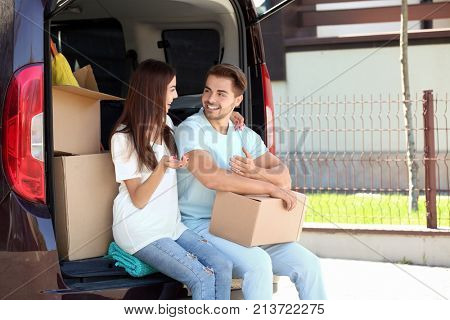 Young couple having break while putting their belongings in car trunk outdoors