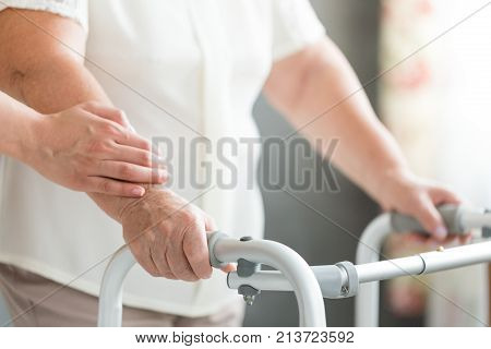 Caregiver Supporting Senior Using Walker