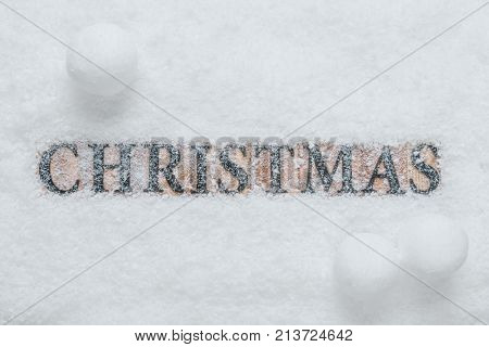 The word Christmas made with wooden letter blocks, on a snow background with snowballs.