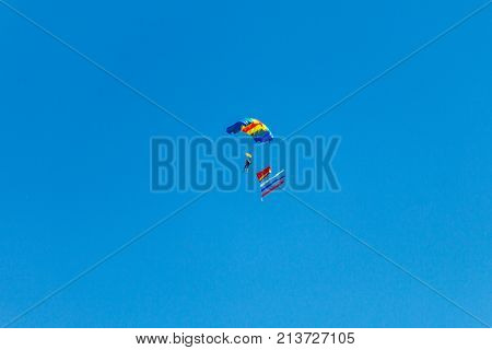 a parachutist jump against the blue sky