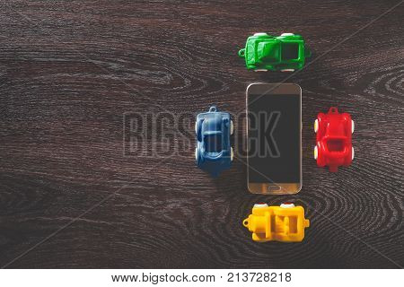 Four cars model and smarphone on dark wooden background with copyspace. concept of car rental, auto car insurance and travelling