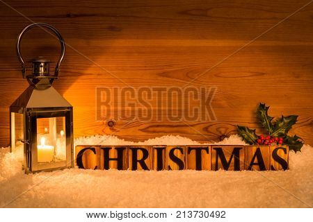 The word Christmas next to lantern with candle inside on a snow and wod background with holly