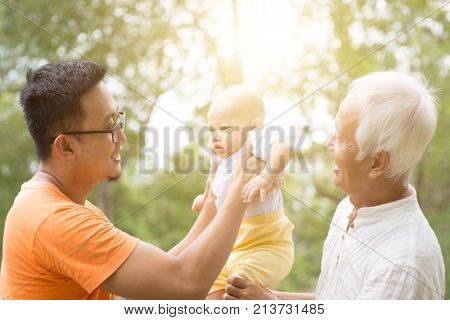 Happy grandfather, father and baby grandchild at outdoors park. Asian multi generations family.