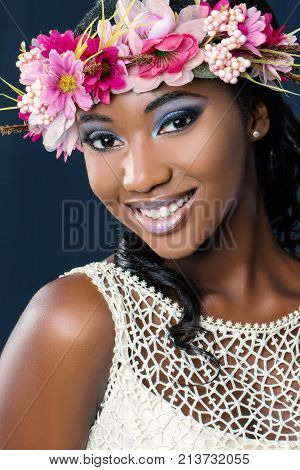 Close up beauty portrait of charming young african bride wearing colorful flower hair wreath.