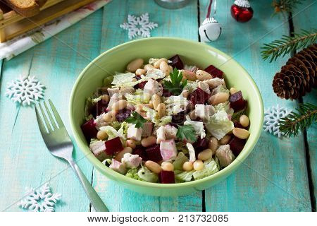 Homemade Appetizer On A Festive Christmas Table. Salad With Beets, Peking Cabbage, Meat And Beans. T