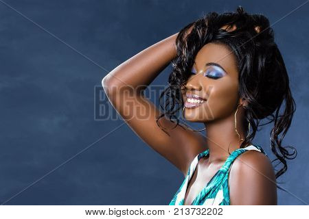 Close up studio beauty portrait of sensual young african woman. Girl with hand in hair and eyes closed laughing. Isolated on dark blue background.