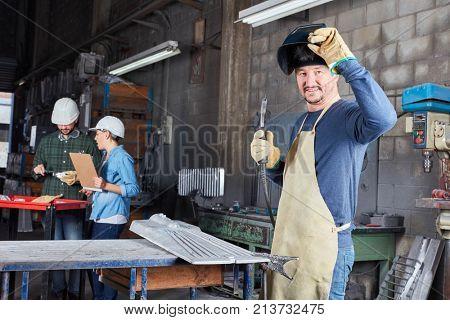 Welder industry worker in metal factory as blue collar worker