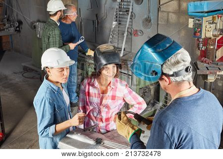Two women in welder apprenticeship learning during metallurgy lesson