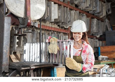 Young woman as blue collar worker apprentice holding metal mold