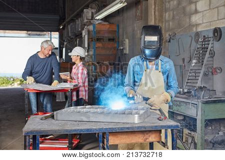 Welder with protective clothing metalworking with flame
