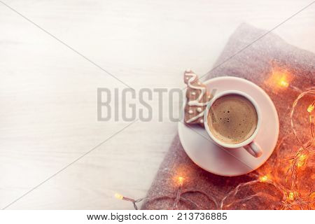 frothy espresso in a cup on a background of blurred lights garlands and figured cookies top view / Christmas coffee break