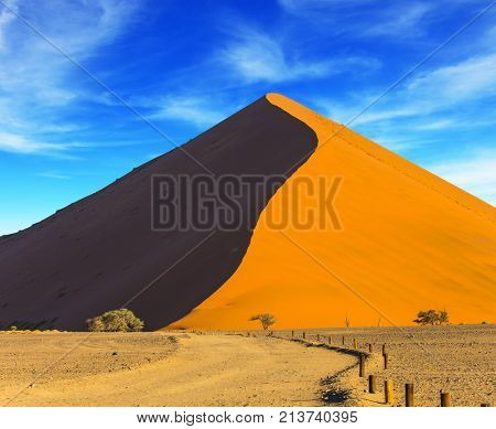 The concept of extreme and exotic tourism. The Namib-Naukluft at sunset. Namibia, South Africa. Sharp border of light and shadow over the crest of the dune