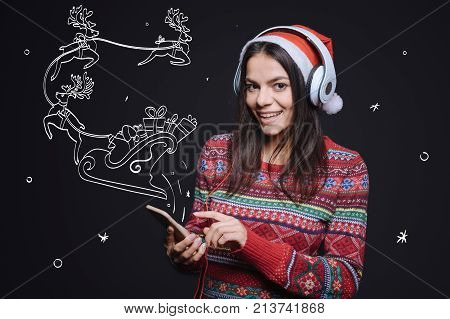 Listening to the Christmas songs. Inspired cheerful young woman standing against imaginary drawing on the black wall and expressing happiness while listening to the music