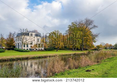 Small river in the Netherlands on a cloudy day in the fall season. The white plastered house was built in 1919 in eclectic style. Now it is a national monument.