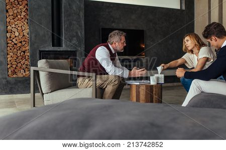 Couple seeing a psychotherapist to solve their relationship problems. Sad woman taking a tissue paper during the therapy session.