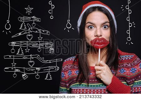 I like Christmas candy. Joyful delighted positive girl expressing joy and holding the lollipops while standing isolated in black background with the imaginary drawing and fooling around