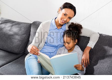 african american mother and daughter reading book together at home