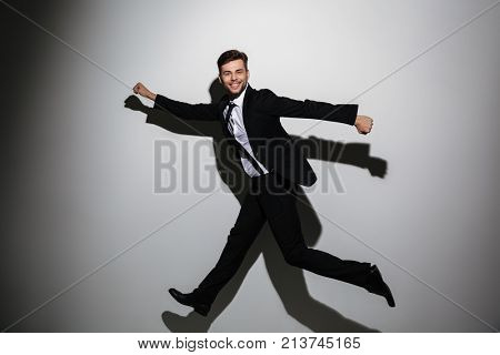 Full lenth photo of happy young businessman jumping in superhero pose, looking at camera, isolated on white background
