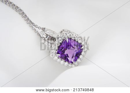 White gold pendant with rose violet amethyst and diamonds on soft blurred background