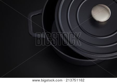 black cast iron pot on black background - food and drink