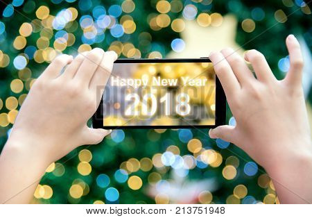 Girl's hand holding mobile phone take a photo of christmas tree with wording Happy New Year 2017. Young woman using smartphone outdoor capture picture of bokeh blur Christmas lighting lamp decoration.