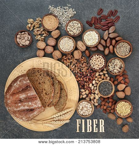 High fiber health food concept with fresh whole grain bread, nuts, seeds, grains and cereals. Foods high in antioxidants, omega 3 fatty acids and vitamins. Rustic background, top view.