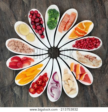 Healthy diet food to promote heart health concept with superfoods of fruit, vegetables and fish providing high levels of omega 3 fatty acids, antioxidants, vitamins and minerals.