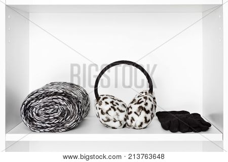 Fashion women accessories. Twisted knitted scarf, faux fur winter earmuffs, black wool gloves on white shelf inside closet. Copy space