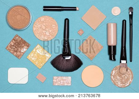 Concealer stick, liquid and cream foundation, correcting, bronzing, highlighting, shimmer golden powder with make up brushes and sponges. Corrective makeup set, flat lay
