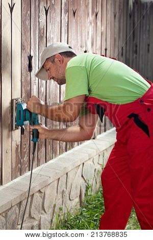 Man refurbishing old wooden fence - removing cracked paint layer with electric vibrating sander machine