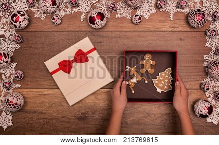 Kids hands giving or receiving christmas gift with various gingerbread cookies