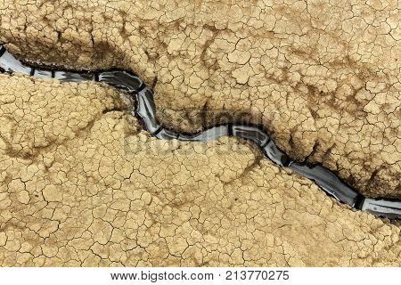 Soil erosion detail - with small gully meandering through cracked earth surface copy space