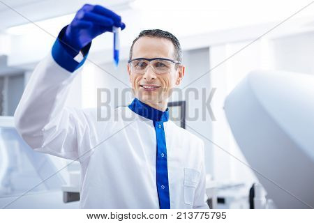 Lets see. Joyfull  determined male researcher jiggling test tube with blue liquid while examining it and standing in the lab