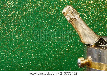 Celebrating new year, birthday, xmas party. Bottle of champagne in a bucket on green backgroud with glitters, copy space. Mockup for postcard