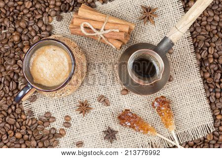 Strong fragrant cooked coffee with foam. A coffee drink in a cup. A cup of coffee sugar on a stick nutmeg on coffee beans. Freshly brewed coffee in a pot. Cinnamon near the cup with coffee and cezve on the burlap top view