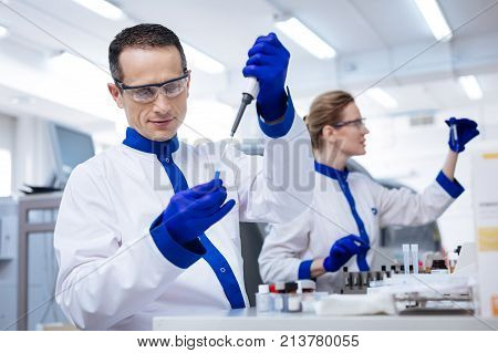 Medical procedure. Interested curious male lab assistant   placing reagent into the glassware with a pipette which located in his hand while looking at liquid attentively