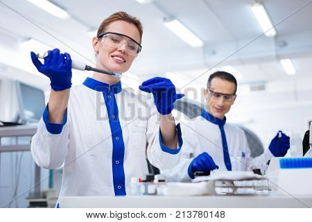 Routine work.  Elegant happy female researcher getting sample from the glassware carefully  while holding up pipette and standing in the laboratory