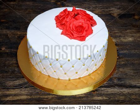 white fondant cake with red cream sugar flowers