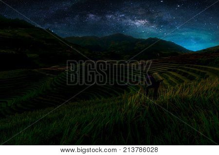 Landscape with Milky way galaxy. Night sky with stars and silhouette Photographer take photo over Rice fields on terraced in Mu Cang Chai. Long exposure photograph.