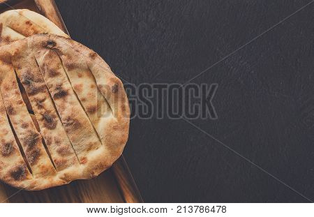 Tandoori bread on black background, copy space. Fresh baked nan, traditional eastern soft tack