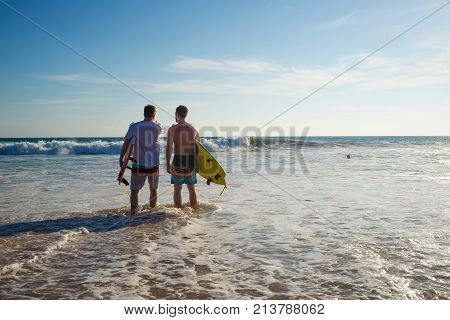 Two Men With A Surfboard On The Beach