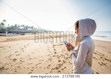 Young Woman Is Listening To The Music On The Phone Before Jogging On The Beach At The Sunrise